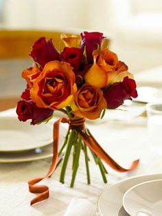 To create this bold bouquet, trim the stems of a dozen roses to 10 inches and strip leaves; with a rubber band, gather the stems just below the heads. Splay out the stems and snip to form a sturdy base; finish with ribbon.