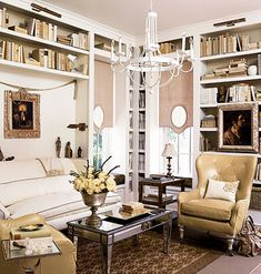 Floor-to-ceiling bookshelves with contrasting interiors accentuate the high ceilings in this cottage parlor.