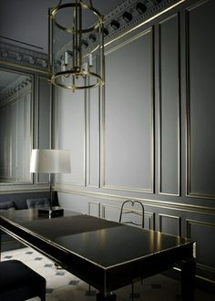 Grey painted ornate paneling with gold leaf on the applied moulding.