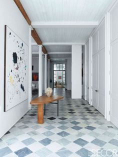 In the entrance, the 1960s table is by Atelier Marolles, and the painting is by Secundino Hernández.
