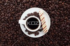 close-up of coffee cup and beans. - Close-up top view of coffee cup surrounded with coffee beans and cookies.