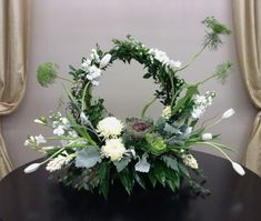 White and green floral arrangement with fresh greenery wreath, tulips, hyacinth, freesia, stock, and ornamental kale by Nancy at Belton Hyvee.