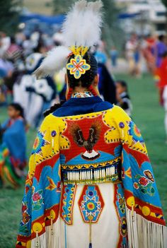 Ladies traditional Pow Wow dancer dressed in white brain tanned leather regalia with beautiful beaded cape with an eagle motif along with a ...