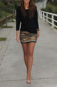 Long plain black shirt and beaded skirt. Nude heels.
