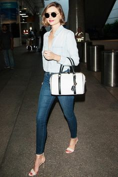 Miranda Kerr wears a Rails Carter button down with Frame Denim jeans, Gianvito Rossi leather sandals, and a Samantha Thavasa bag
