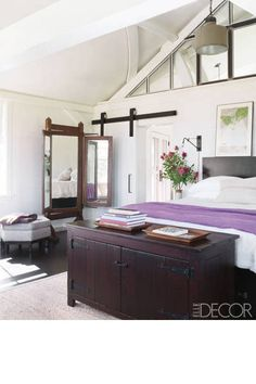 The light-filled master bedroom of Meg Ryan's home on Martha's Vineyard is all about ease. Vintage linens, simple lighting, and a barnstyle sliding door create a rustic feel. The custom-made bed and trunk were designed by Marsha Russell of Satinwood and made by Herrick & White , and the sconce is by O'Lampia Studio.   - HarpersBAZAAR.com