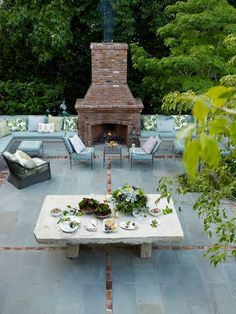 """For outdoor dining, the bluestone and old brick patio features an eight-foot antique Dalle de Bourgogne stone table """"that was probably used for threshing wheat,"""" says Dunham, who designed the neoclassical iron furniture. Victoria Pearson  - HouseBeautiful.com"""