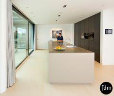 De prachtige moderne greeploze keuken, heeft een keramisch aanrechtblad met een marmer look.