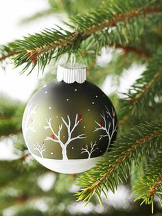 Scenic Ornament: It's easy to create this winter scene on an ornament. The trick is to paint in steps. First, paint the bottom of a glass ball ornament with two coats of white acrylic paint; let dry after each coat. Then use a small, round brush to paint white trees in different sizes. Once the trees have dried, add small dashes of red acrylic paint to the trees to resemble cardinals. After the red paint has dried, use the bristle tips to add small white dots for falling snow.
