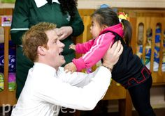 Prince Harry picks up a young girl during a visit to a kindergarten for indigenous children in Santiago, Chile.