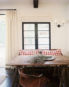 black window encasements + white walls + dark wood floors + aged wood table + lavendar