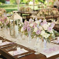 rustic tables topped with arrangements of garden roses, tulips and hydrangeas. Monogrammed silver runners and lanterns also dressed the tables. In addition, each place setting had vintage silverware and an embroidered lace napkin.