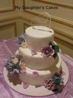 Three-tier wedding cake with roses in wisteria and lavender.  The cake is embellished with scroll piping.