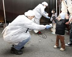 Officials in protective gear check for signs of radiation on children from the evacuation area near the Fukushima Daiichi Nuclear Power Plant in Koriyama, on March 13, 2011.