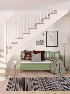 Under trappan kan man slå sig ner i en grönmålad kökssoffa med mörkröda kelimkuddar från Carpetvista och Afro Art. Ljusstake, Granit. Pläd, Ikea.