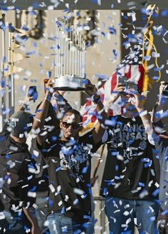 Kansas City Royals' Alcides Escobar stands with the trophy during Tuesday's Kansas City Royals baseball World Series celebration on November 3, 2015 at Union Station in Kansas City, Mo.