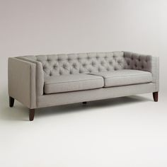 Large, comfortable and full of mid-century style, our Fog Kendall Sofa is both polished and practical. Constructed of mixed hardwoods, it features hand-tufted detailing on the back and arms, shelter arms, espresso-finished tapered wood legs, and durable polyester blend upholstery in a neutral medium gray.