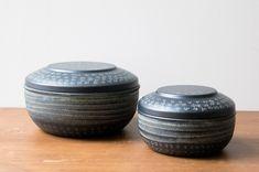 Ces jolies boîtes rondes gravées sont de la marque danoise Madame Stoltz. En métal noir, elles sont incrustées de petits signes blancs, qui rappellent les caractères utilisés dans l'alphabet chinois.
