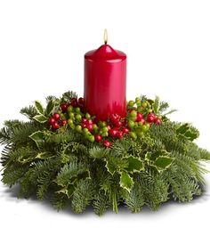 A Berry Bright Christmas: an inviting arrangement features green hypericum with noble fir, seeded eucalyptus, variegated holly, flat cedar and faux red berries – delivered with a red pillar candle.