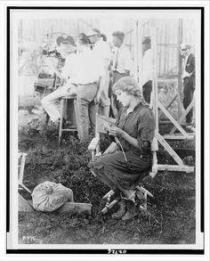 Mary Pickford knitting a sweater for the American Red Cross, with movie film crew behind
