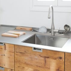 Behind the sink is a stainless steel dish drying rack, slotted storage for wood cutting boards, and two caddies for kitchen utensils.