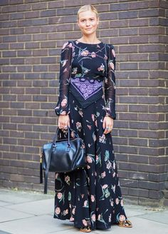 Pandora Sykes wears a floral maxi dress with a bandana tied around the waist, snakeskin boots, and a black leather duffle purse