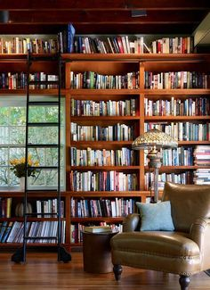 Vintage Library: Floor to ceiling bookshelves with a libary ladder, a Tiffany style lamp, and a cozy leather chair to curl up and read. Perfection. Photo Credit: One Kind Design