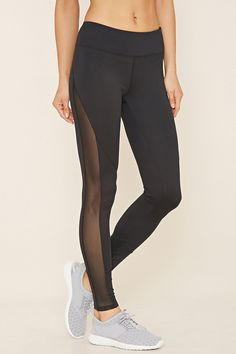 A pair of stretch knit athletic leggings with moisture management, a hidden key pocket, and a sheer mesh panel down the side of each leg.