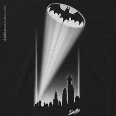 BATSEÑAL Nuestra interpretación de la Batseñal, la llamada que usa la ciudad de Gotham cuando necesita a Batman. Sobre camiseta negra en la ilustración se ve el haz de luz que emerge de el skyline de Gotham con un murciélago al final. Todo en colores blanco y grises. www.diablocamisetas.com