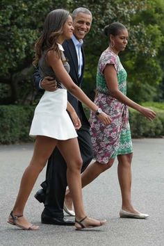 President Barack Obama, center, walks with first lady Michelle Obama, right, and their daughter Malia from the the White House to the Marine One helicopter in Washington, on Saturday. The first family is scheduled to spend 16 days at Martha's Vineyard, though Obama will fly back to Washington during the middle of the trip for meetings
