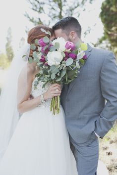 cute photo idea for a wedding - bride and groom kissing behind bouquet!
