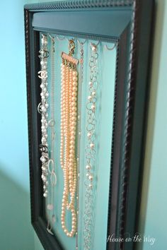 DIY jewelry holder made with an empty picture frame and cup hooks.