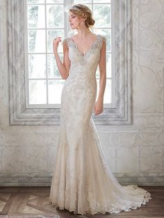 Maggie Sottero - ELISON, This delicate, feminine gown features an exquisitely sequin embroidered lace gown with shimmer metallic threading and plunging back, embellished in illusion lace. Stunning Swarovski crystals and opalescent pearls adorn the illusion cap-sleeves and back of this sheath wedding dress. Complete with crystal button over zipper closure.
