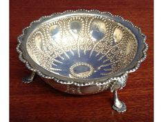 A Victorian Thomas Smily silver bon-bon dish, intricate hand-hammered detailing to centre, beaded rim, resting on three shell feet in the form of stylized human faces (London, 1875).