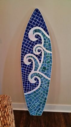 Beautiful wave design mosaic surfboard.  This board is made to order, photos shown are past surfboards in the wave pattern  I hand cut the surfboard shape out of 3/4 plywood and sand the edges to be as smooth as humanly possible. I apply a mosaic of gorgeous stained glass pieces that wrap around the edges and it is finished with white grout.  My mosaics are very organic in that all pieces of glass are hand cut.  Almost 5 1/2 tall.... 66 tall x 19 wide x 3/4 deep and weighs righ...