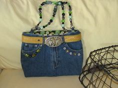 This blue jean purse is 9 1/2 inches long x 12 inches wide.  It has flexible sides and a supportive bottom.  Inside material has green and yellow flowers with a black background.  There is a magnetic snap for closure. Handles are made up of an assortment of glass, metal and plastic beads. The outside of the purse is decorated with a yellow leather belt and green, yellow and black decorations on front and back of purse.  There are 4 outside pockets. $152.00 + Tax, shipping & handling