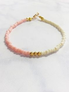 This wonderful friendship bracelet is made with pink, beige and gold beads. A beautiful and gentle color combination looks great and can be stacked with other b