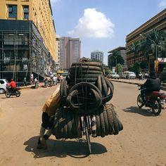 A man transports tires on his bicycle. Kampala, Uganda