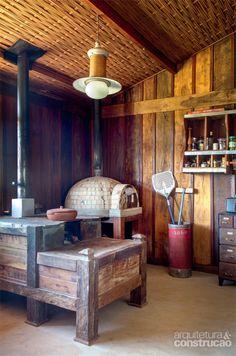 Chalé de madeira de demolição tem vista arrebatadora da serra - Lado a lado, o forno a lenha e o de pizza aquecem o ambiente nos dias frios. No teto, a treliça artesanal de piaçava é uma criação de Sonia Infante (Arteiro).