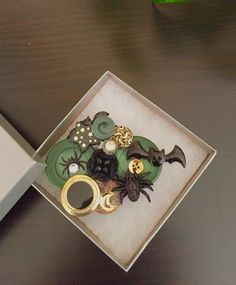 A Holloween brooch created with green and black buttons and Holloween figures by OnTheButtonPath on Etsy