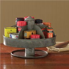 """<p>This versatile piece is great for organizing spices, desk accessories, makeup, or craft supplies; useful in your farmhouse, country, or primitive kitchen, office, or bath. Swivels for easy access. Metal with an aged tin finish. Dimensions: 7.25""""H x 10.25""""Dia</p>"""
