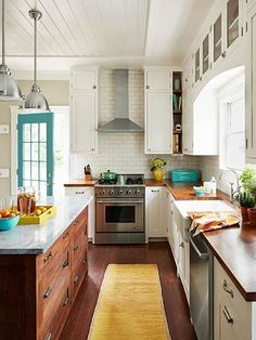 This gorgeous cookspace is the winner of our best kitchen redo in TOH's Search for America's Best Remodel 2015 contest. See the story here. Love the teal door, wood island and white cabinets #whitekitchen #teal