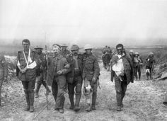 A German prisoner helps escort wounded British soldiers to a medic following fighting on Bazentin Ridge in 1916.