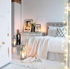 Makuuhuoneen romanttinen valkoinen ilme täydentyy lyhtyjen ja koristevalojen luomasta tunnelmasta