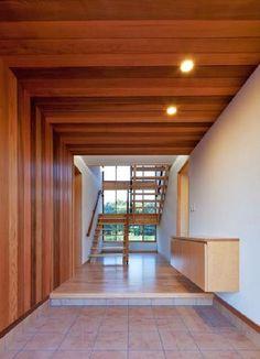 玄関ホール。天井と壁にもレッドシダーを使用している。くつを脱いで上がる形式や、正面に木製階段があるつくりなどが住宅風(写真:インテグラル)