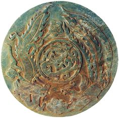 "Ancient Chinese. Carved variegated green jade disc with a central low-relief dragon in the center, two dragon like animals on the outer rim.  200 AD (11 ¾"")"