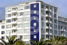 Modern apartments in Eastbourne with palms  in the forefront and a view of the sea.
