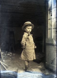 Vintage photo of little boy smoking a corn cob pipe in an abandoned-looking building. Possibly Edwardian. Unbelievable photo.