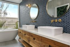 The warm walnut vanity pops against the stunning navy hexagon tiles - what a bathroom.