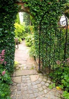 Wrought iron arched garden gate in a red brick wall with stone flagged path leading to seperate garden rooms
